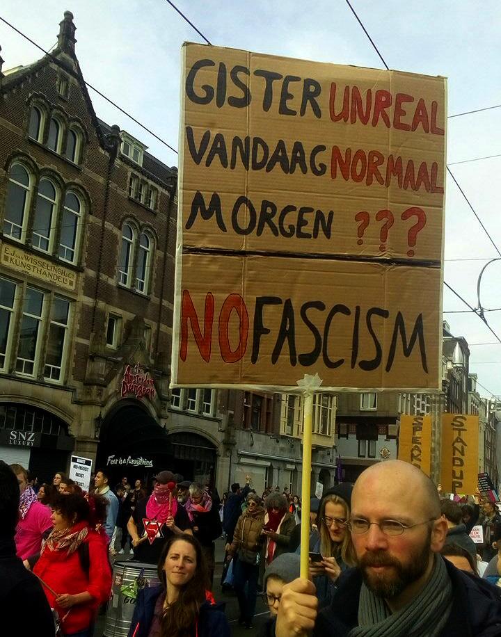 """Een persoon met een bril en een baard houdt een kartonnen bord vast met daarop de tekst """"Gisteren unreal - vandaag normaal - morgen ??? / No fascism""""."""