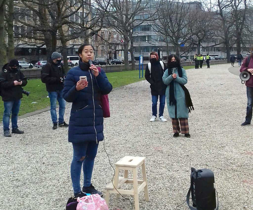 Een persoon met lange zwarte haren en een bril in een driekwart lange jas spreekt via een microfoon. Enkele omstanders luisteren.