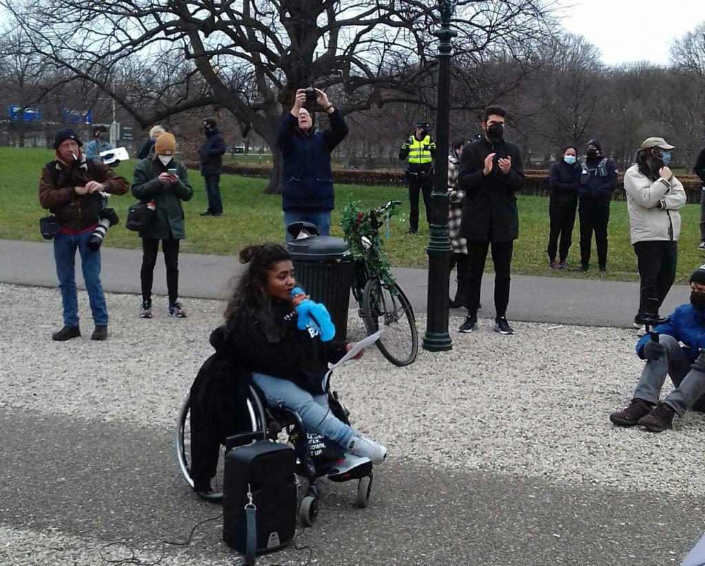 Chedda, een bruin persoon met lange zwarte haren, een zwarte trui en een lichte spijkerbroek, zit in een rolstoel en houdt een toespraak. De omgeving is park-achtig, met een fietspad, een kiezelpad, gras en bomen op de achtergrond. Om haar heen staan diverse toehoorders waaronder een fotograaf met een grote telelens bij op de heup. De meeste mensen dragen mondkapjes. Op de achtergrond een politiebeambte met een veiligheidshesje aan.