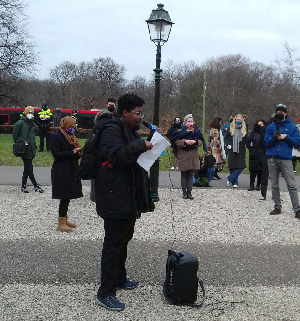 Een zwart persoon met kort haar, een donkere jas, een rugzak en een bril geeft een speech via een microfoon. De persoon leest tekst van een briefje. Op de achtergrond rijdt de tram voorbij.
