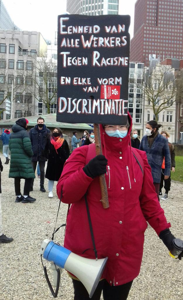 """Een warm ingepakte persoon met een rode jas aan en de capuchon over het hoofd met een bord met de tekst: """"Eenheid van alle werkers tegen racisme en elke vorm van discriminatie""""."""