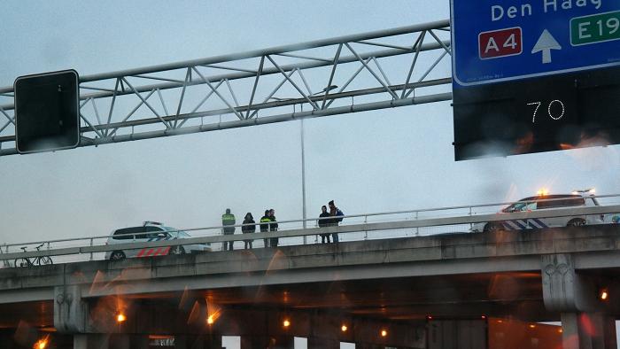 Politie en omstanders nadat het spandoek over de A4 zojuist verwijderd was.
