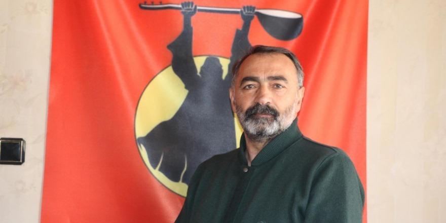 Portret van Turgut Öker. Hij heeft grijzend zwart haar en een baard en snor. Hij draagt een donkergroene gebreide trui.