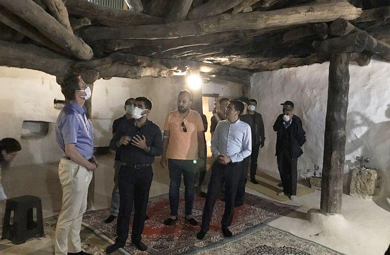 Een groep mannen met mondkapjes staat in het oude cemhuis. Het plafond is van oude houten balken. De muur is onregelmatig van structuur en witgekalkt. Op de lemen vloer liggen tapijten. Tegen de wand twee stenen wasbakjes.
