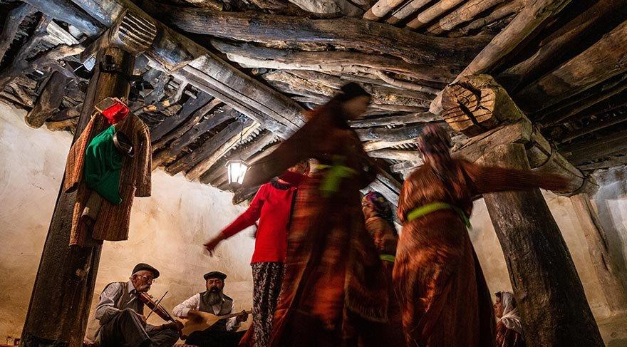 Twee mensen in het cemhuis maken muziek met snaarinstrumenten terwijl enkele anderen dansen op de muziek.