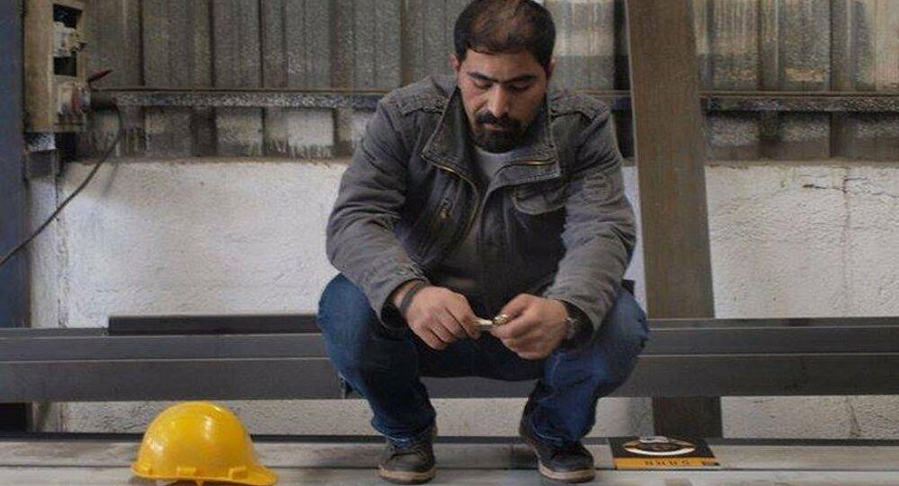 Foto van Ethem Sarisülük die op zijn hurken zit. Naast hem ligt een bouwhelm.