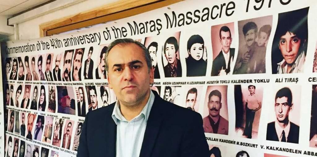 Foto van İsrafil Erbil. Hij staat voor een wand met portretten van mensen die omkwamen bij de slachting in Maraş.
