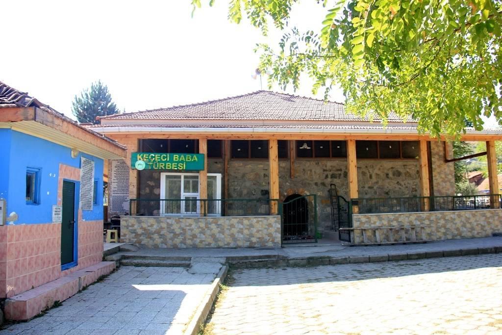 Schrijn van de alevitische heilige Keçeci Baba. Een gebouw in hout en natuursteen met een rood pannendak. Er is een ronde poort die toegang biedt.