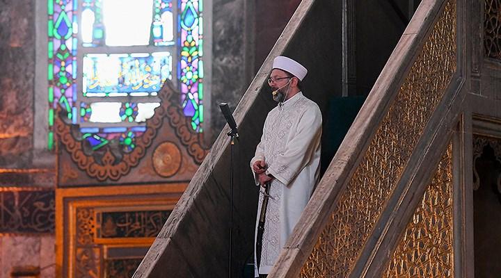 Een imam in een moskee. Op de achtergrond een prachtig, kleurrijk glas-in-lood raam. De imam draagt een crèmekleur gewaad dat rijkelijk geborduurd is. Hij spreekt de gelovigen toe via een micofoon.