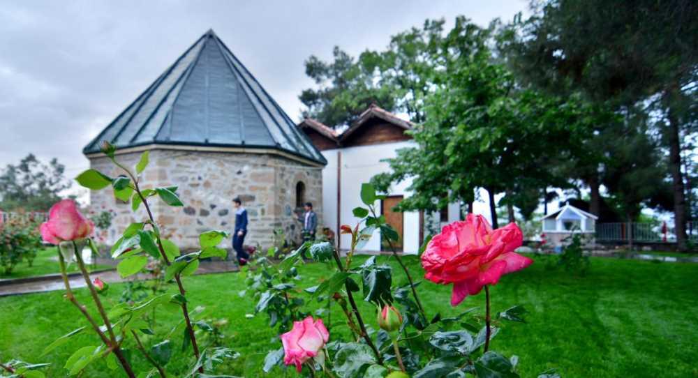 Schrijn van Koyun Baba. Een zeskantig natuurstenen gebouwtje met een puntig zinken dak. Op de voorgrond van de foto bloeiende rozen.