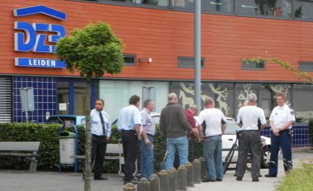 De situatie toen we aankwamen lopen. Van links naar rechts twee bewakers met de blauwe overhemden, twee medewerkers van het centrum, een klusjesman met de paarse trui, twee bouwvakkers met witte t-shirts en twee agenten met witte overhemden.