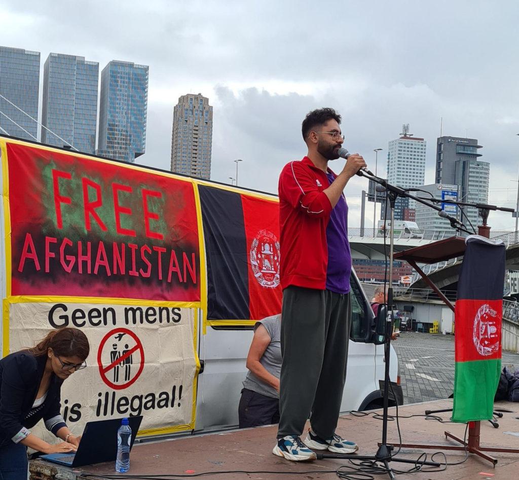 Akef aan het woord op het podium. Akef draagt een grijze joggingbroek, een paars shirtje en een rood vest. Hij heeft zwarte krullen en een baardje. Op de achtergrond de hoogbouw van Rotterdam.