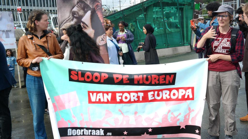 Twee demonstranten met een Doorbraak-spandoek met de tekst 'Sloop de muren van Fort Europa'.
