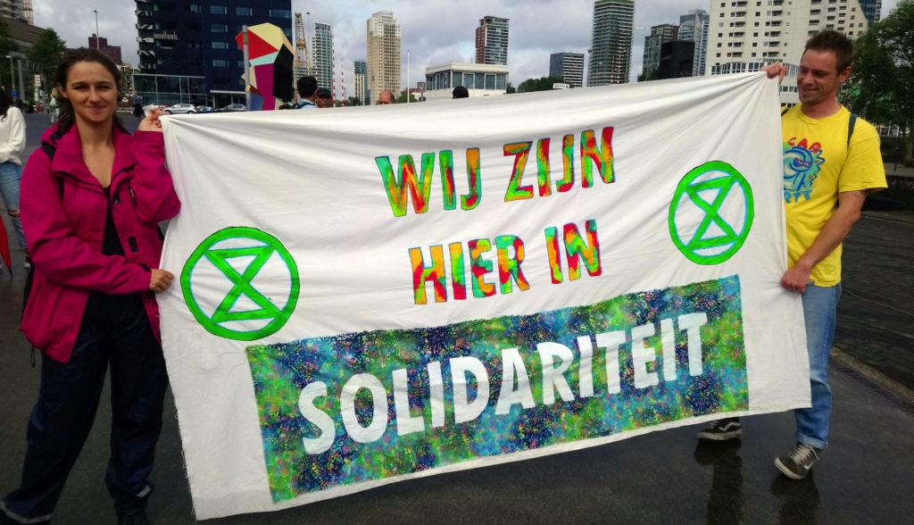 Kleurrijk spandoek van XR met de tekst 'Wij zijn hier in solidariteit'.
