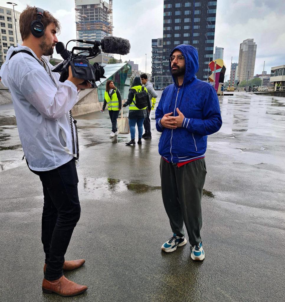 Akef wordt geïnterviewd. Het regent en Akef heeft zijn capuchon opgedaan. De journalist draagt een witte regenjas en filmt Akef.