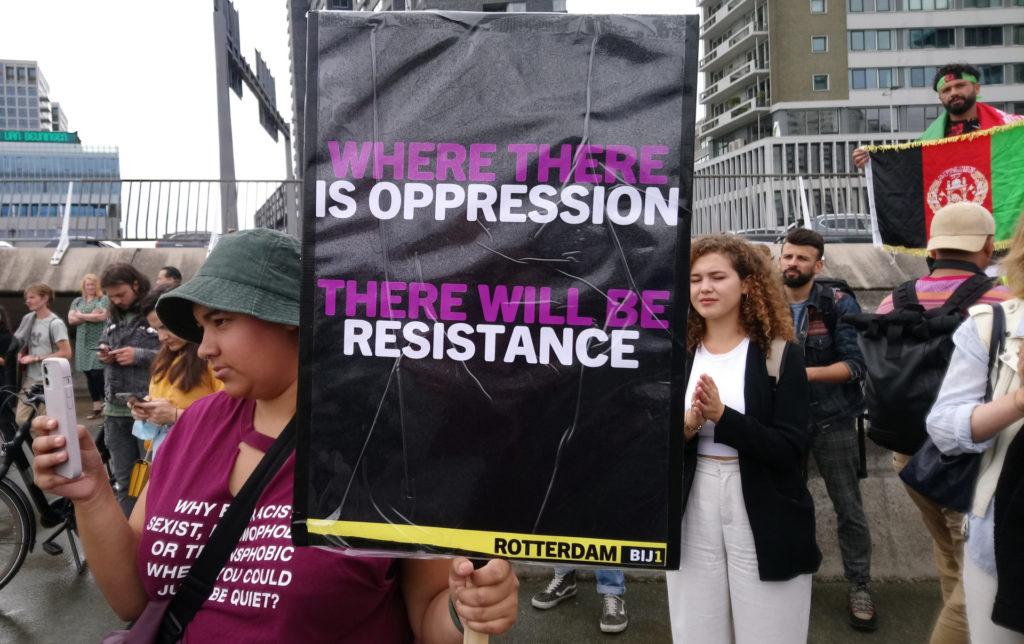 Een demonstrant met een BIJ1-protestbord met de tekst 'Where there is oppression, there will be resistance'.
