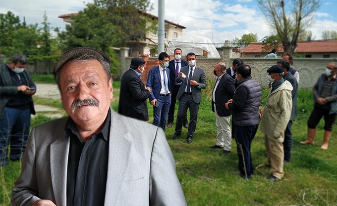 Mehmet Turan. Hij draagt een grijs pak, een zwart overhemd en een ouderwetse pet.