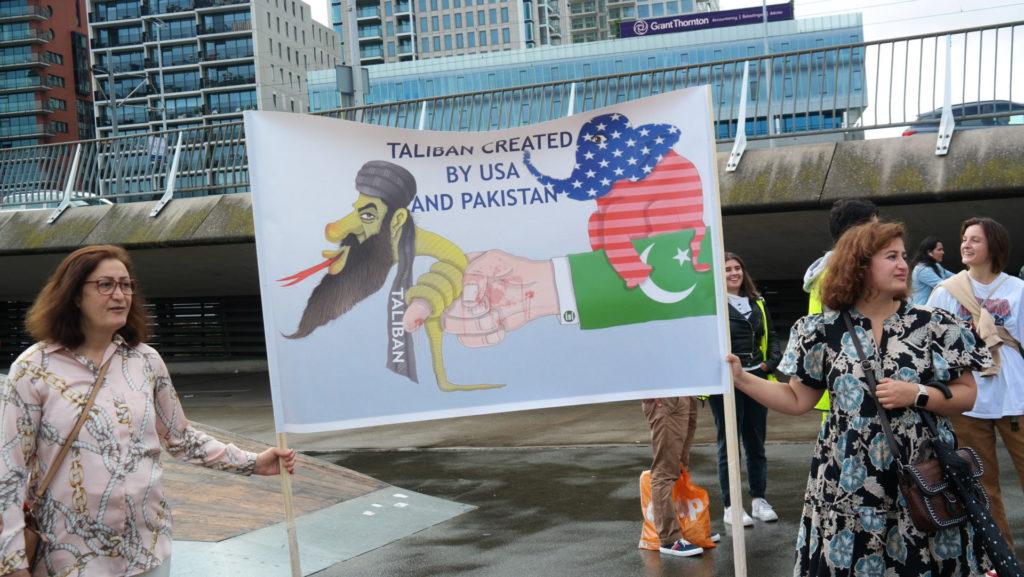 Een spandoek met daarop een spotprent van een Taliban-strijder in de vorm van een slang, die om een bloedende vinger gewikkeld zit. De hand zit aan een arm met de Pakistaanse vlag. Op de arm zit een Amerikaanse olifant.