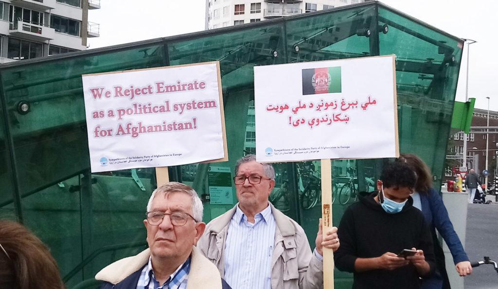 Twee oudere demonstranten, waarvan eentje met een bord met de tekst 'We reject Emirate as a political system for Afghanistan'. De andere draagt ook een bord, maar in een taal die ik niet kan lezen.