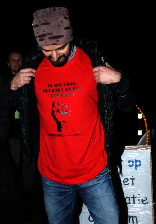 """Activist met een van de vijf nieuwe T-shirts: """"Ik wil loon, rechten en een contract"""""""
