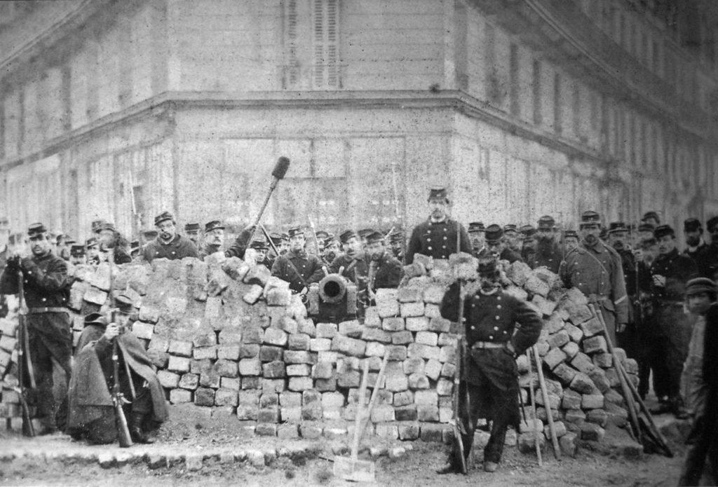Zwart/wit foto van een barricade met een kanon met leden van de Nationale Garde eromheen.