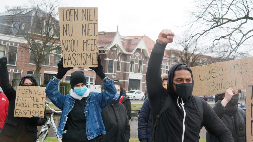 """Demonstranten bij een Leids protest tegen Baudet. Ze hebben hun vuist in de lucht. Op kartonnen borden staat te lezen """"Toen niet, nu niet, nooit meer fascisme"""" en """"Weg met Baudet""""."""