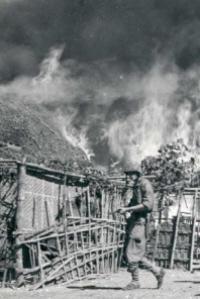 Nederlandse militair bezig met platbranden Indonesisch dorp.