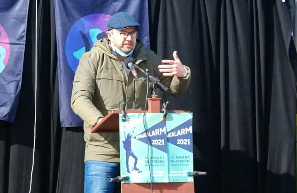 Foto van Christian Henderson die achter een lessenaar een speech geeft bij het Klimaatalarm in Leiden. Christian draagt een tweed pet en een legergroene warme jas. Op de lessenaar hangt de mintgroene poster van het Klimaatalarm 2021.