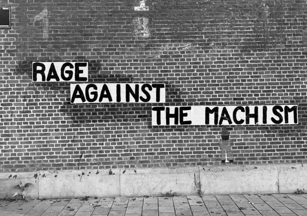 """Zwartwitte afbeelding van een bakstenen muur met daarop de tekst """"Rage against the machism"""". Er is een poppetje op de muur getekend dat naar de tekst kijkt."""