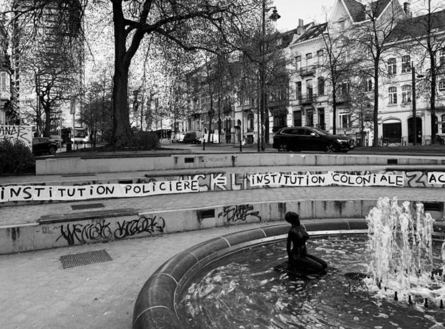 """Een fontein op de voorgrond met een vrouwelijk naakt erin. Op de achtergrond een trap waarop de tekst """"Institution policiere / institution coloniale"""" staat."""