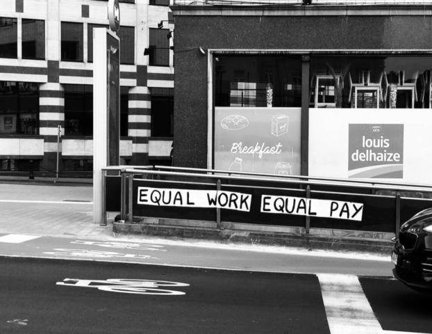 """Een supermarkt langs de kant van de weg met ervoor een metro-ingang met daarop de tekst """"Equal work equal pay""""."""