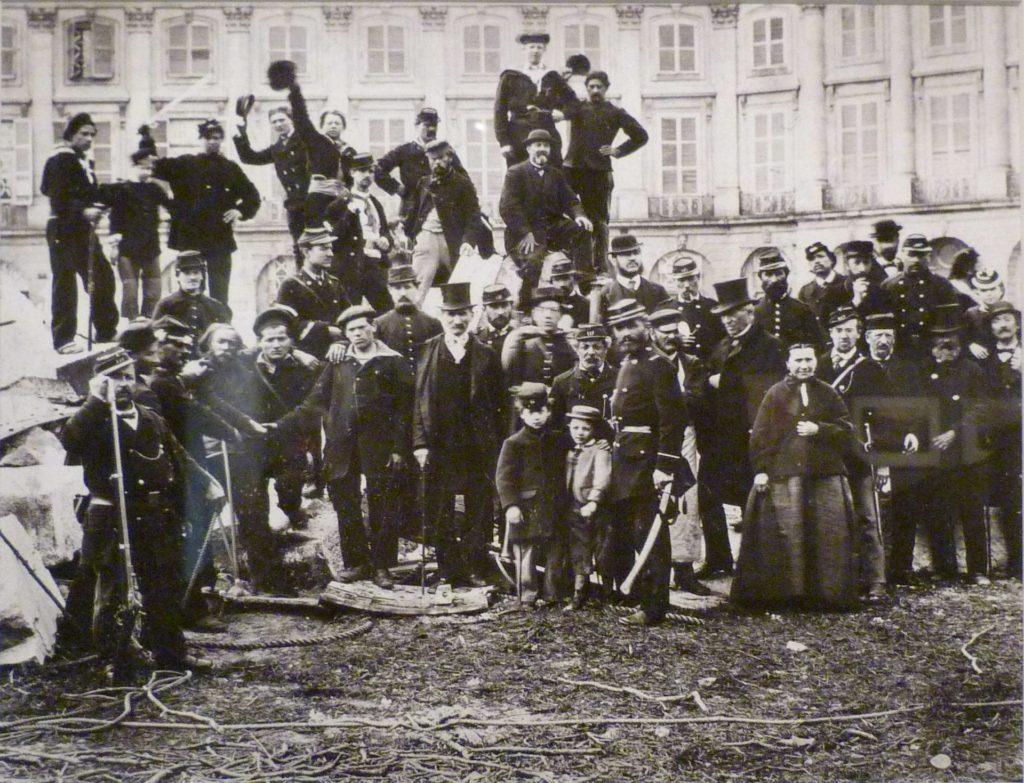 Een poserende groep deelnemers aan de Commune van 1871. Iedereen draagt donker gekleurde kleding. Op de voorgrond twee kinderen en een vrouw met een wijde rok. Achteraan staan mensen op een verhoging. Sommigen nemen hun pet af voor de foto.