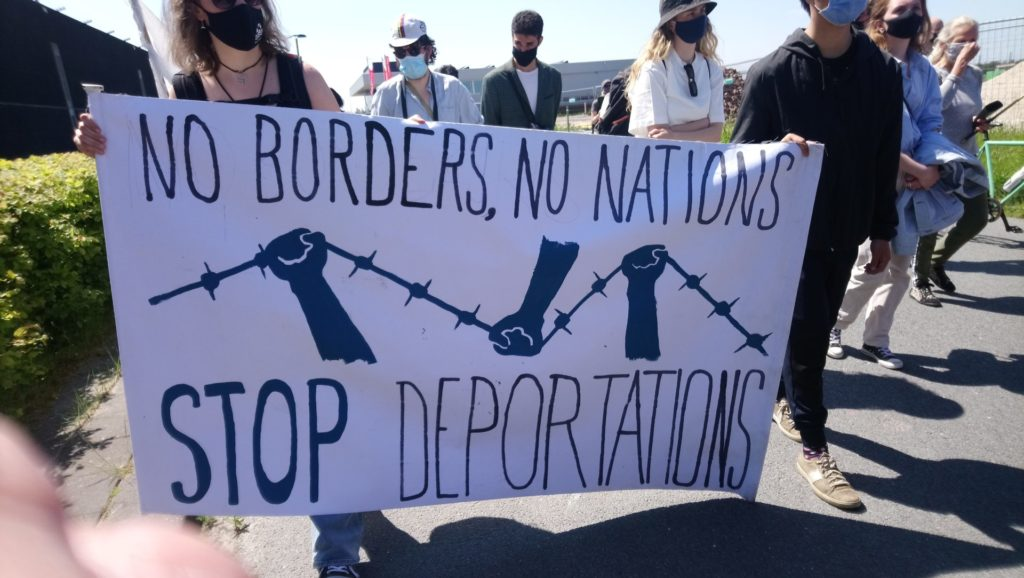 """Spandoek met de tekst """"No borders - no nations - stop deportations"""". Erop afgebeeld drie vuisten die prikkeldraad kapot trekken."""