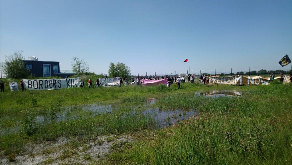 De deelnemers gezien vanaf de andere kan van een grasveld. Het is een grote groep mensen.