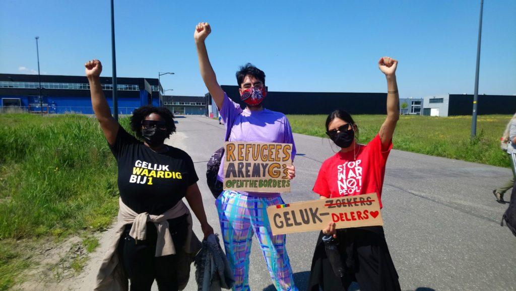 """Drie demonstranten met de vuisten in de lucht. Eentje draagt een """"Gelijkwaardig BIJ1"""" shirt, eentje heeft een bord met de tekst """"Refugees are my G's - open the borders"""" en eentje draagt een shirt met de tekst """"Stop war not people"""" en een bord met de tekst """"Gelukzoekers"""" waarbij 'zoekers' is doorgestreept en vervangen door 'delers' met een hartje erachter."""