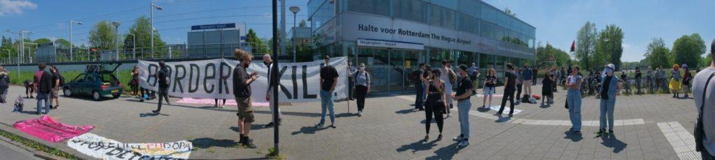 """Breedbeeldfoto met daarop het enorme spandoek """"BORDERS KILL"""" en een deel van de demonstranten."""