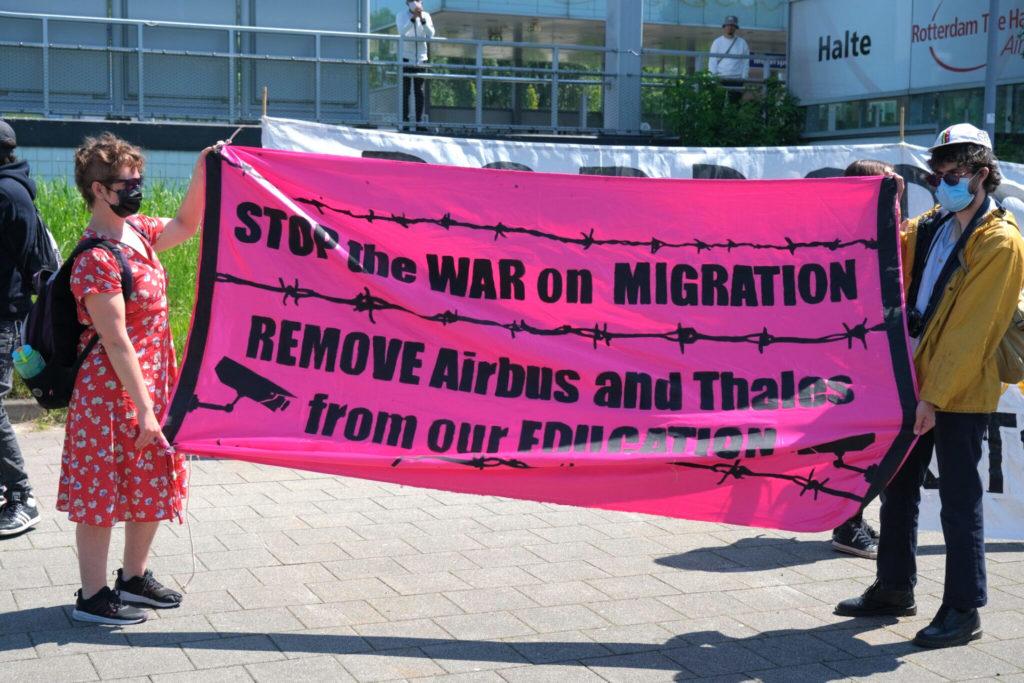 """Twee deelnemers met een knalroze spandoek met de tekst """"Stop the war on migration - remove Airbus and Thales from our education""""."""