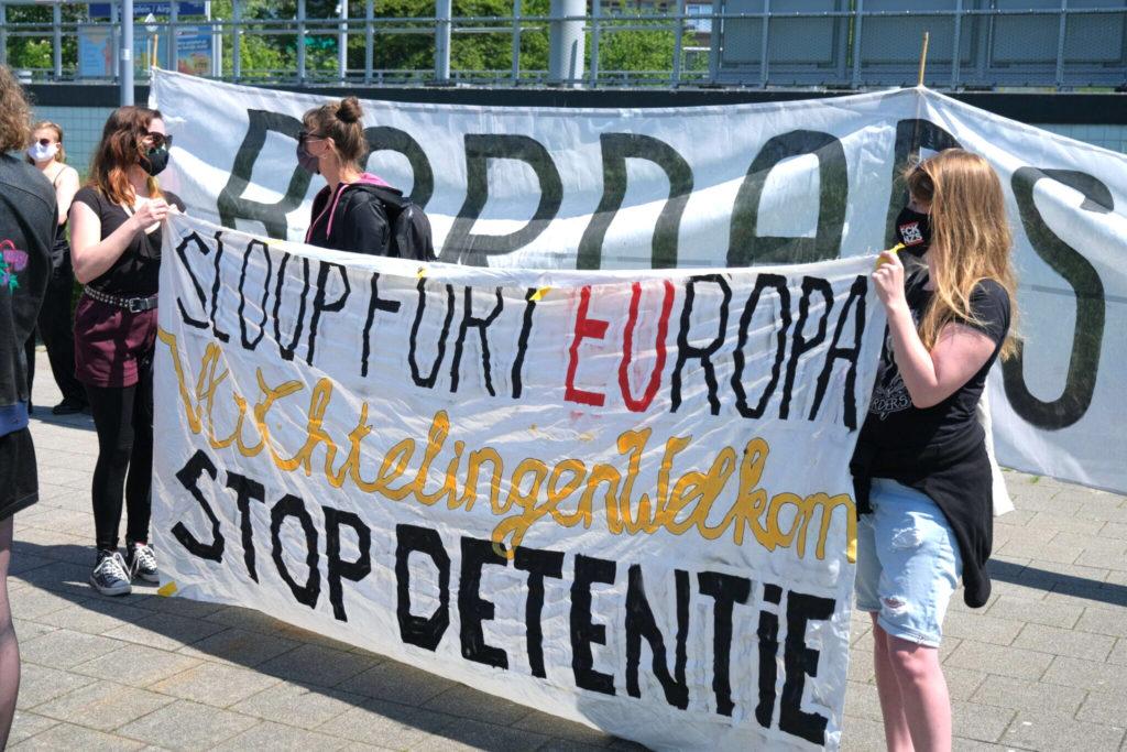 """Demonstranten met een spandoek met de tekst """"Sloop Fort Europa - vluchtelingen welkom - STOP DETENTIE""""."""