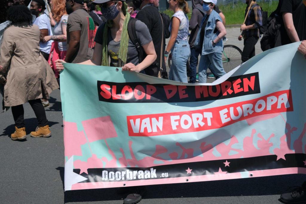 """Doorbraak-spandoek in mintgroen en zachtroze met de tekst """"Sloop de muren van Fort Europa""""."""