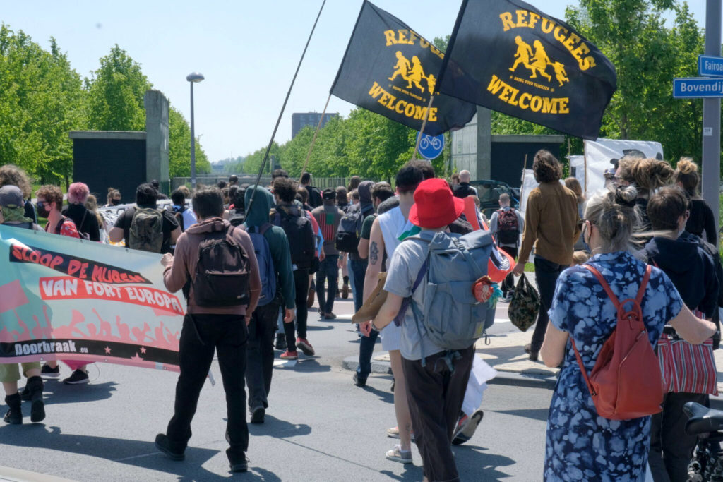 """Overzicht van de deelnemers. Twee mensen dragen """"Refugees welcome"""" vlaggen aan lange stokken."""