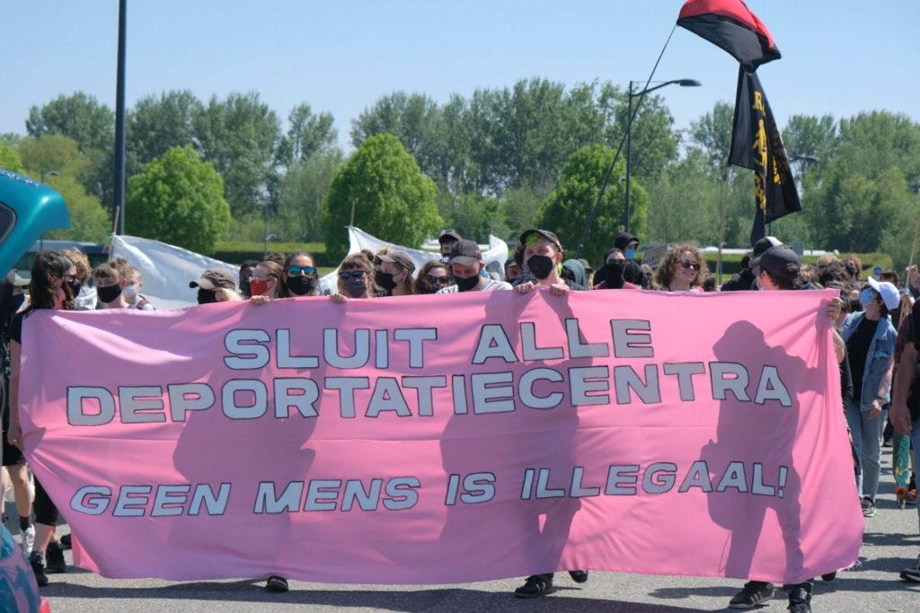"""Groot roze spandoek met de tekst """"Sluit alle deportatiecentra - geen mens is illegaal""""."""