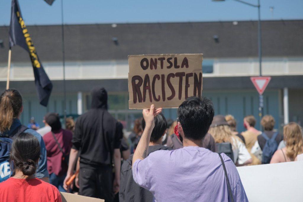 """Demonstrant met een bord """"Ontsla racisten""""."""