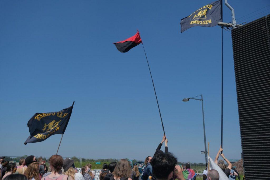 Mensen zwaaien met vlaggen op lange stokken zodat de gevangenen het kunnen zien.