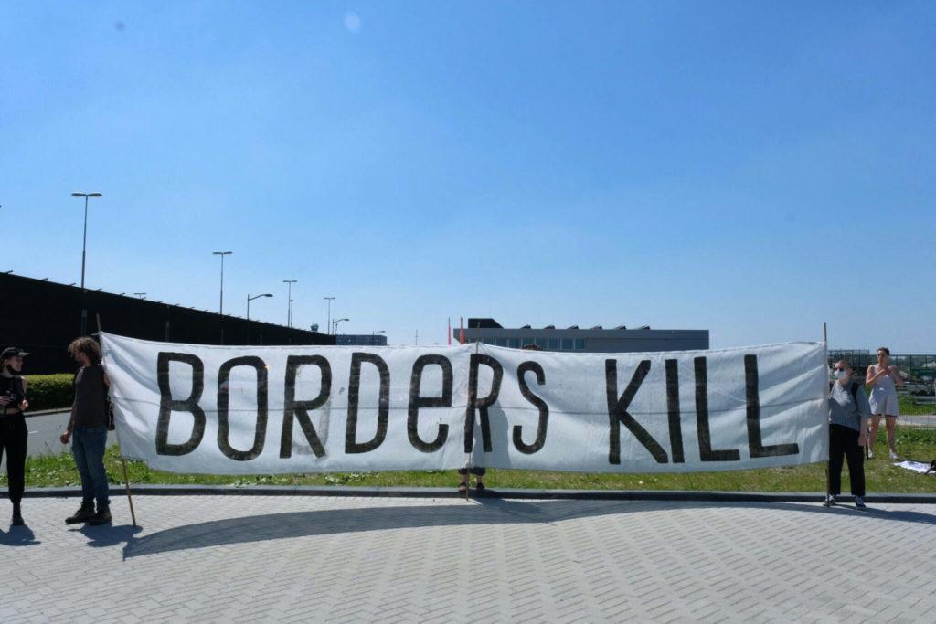 """Beeld van het gigantische """"BORDERS KILL"""" spandoek."""
