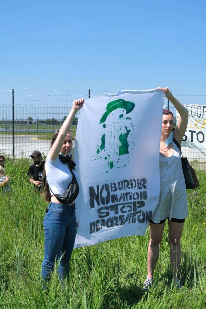 """Twee mensen met een spandoek met daarop een beertje met een koffer en de tekst """"No border no nation stop deportation""""."""