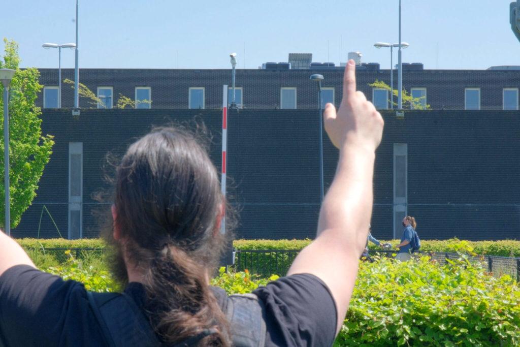 Een demonstrant heft de handen op richting het detentiecentrum.
