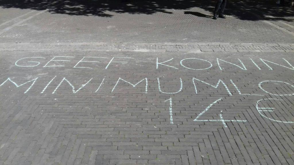 """Krijttekst """"Geef koning minimumloon € 14"""""""