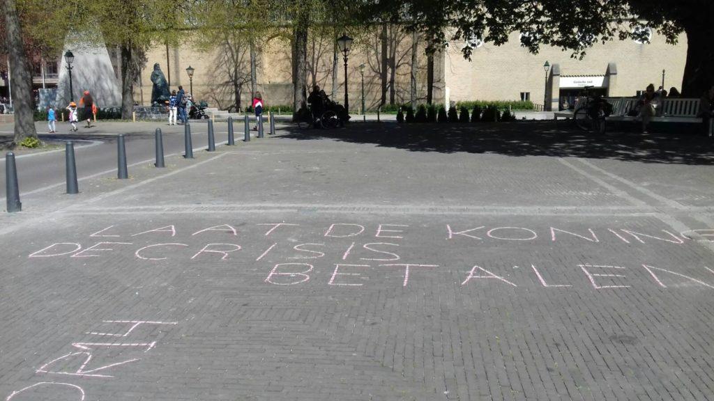 """Krijttekst: """"Laat de koning de crisis betalen"""""""
