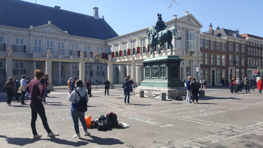 Voor het paleis kijken allerlei voorbijgangers wat er op de bestrating geschreven staat.