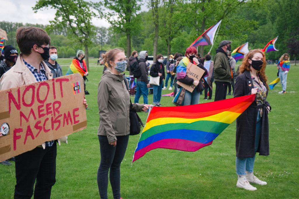 Twee deelnemers houden samen een regenboogvlag vast.